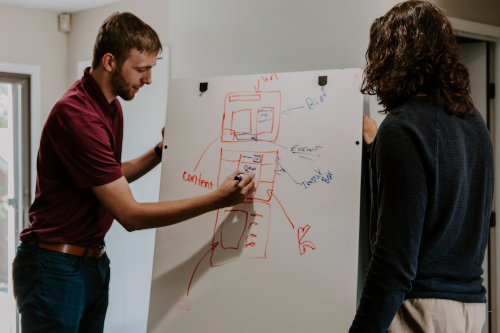 content is king man drawing on a whiteboard with website design